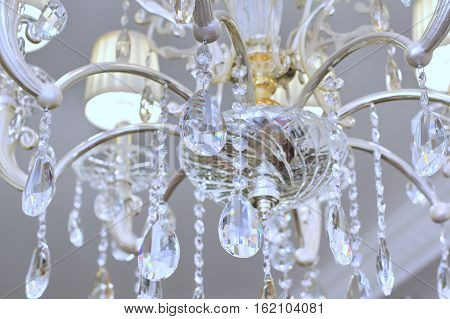 A Chrystal chandelier close-up. Glamour white light background with copy space