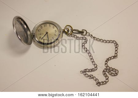 old pocket watch and chain, and a hinged lid on a white background