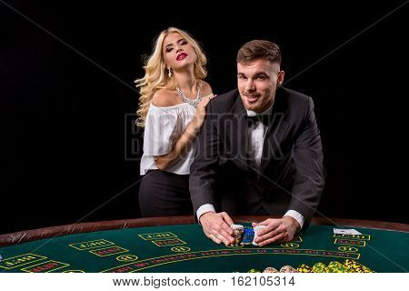 View of young, confident, man with the lady while he's playing poker game. They both look at the camera and smiling