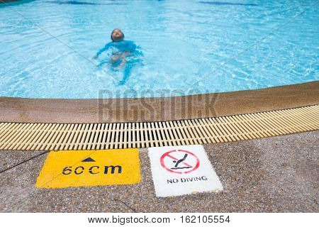warning and depth sign at swimming pool for children with blurred kid swimming in background