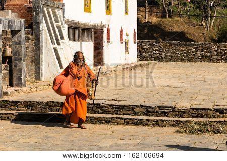 Bandipur, Nepal - NOVEMBER 24, 2016: Nepali aged pilgrim in orange robe in the temple of Bandipur in Nepal November 24 2016.
