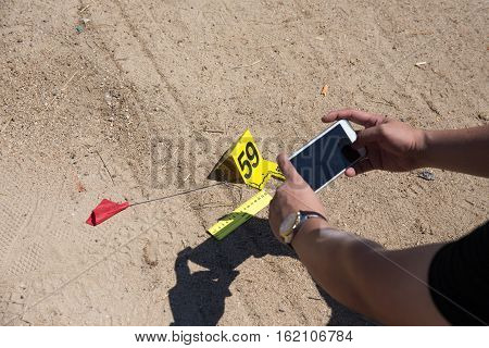 law enforcement or forensic take picture of evidence from car bomb with marker and ruler by smart phone in post blast investigation training