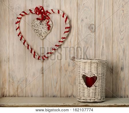 Decor heart and candlesticks from the vine on a light wooden background.