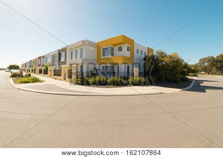 Asphalt road with modern terrace house in front on blue sky background. Yanchep Beach Town Perth Western Australia .