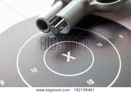 close up ' x ' on bullseye paper shooting target with blurred silver .45 pistol barrel background