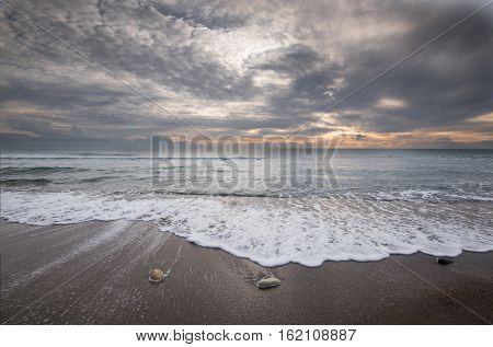 Pebbles on the beach and flowing sea water during sunset creating nice textures. Long exposure image.