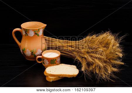 Slices of white bread a cup of milk and a jug a sheaf of wheat ears on a black table
