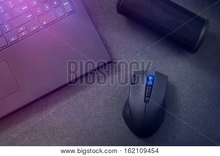 Gaming mouse portable speaker and laptop at night.