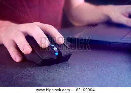 Man holding gaming mouse and laptop screen glowing at night. Nightlife conception