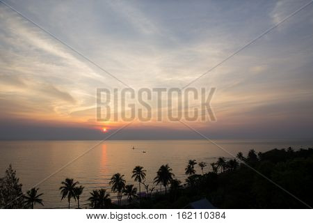 sunrise and sillhouette coconut tree at Hua Hin beach and sea in Thailand