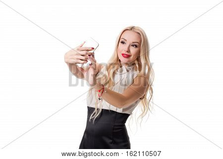 Young blonde doing selfie on isolated white background. Selfie time. Young woman in black and white dress