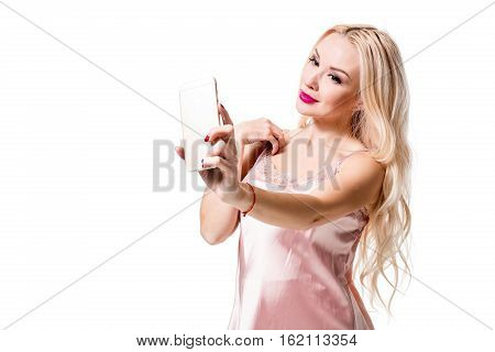 Young blonde doing selfie on isolated white background. Selfie time. Young beautiful woman in silk dress
