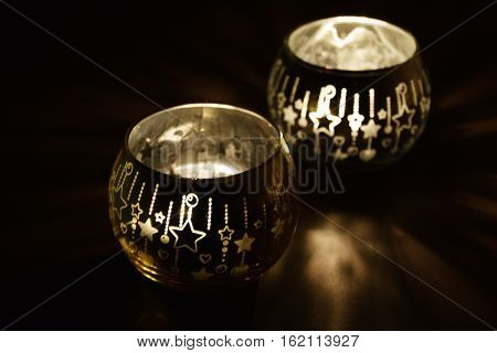 Christmas candles burning in the dark with shadows
