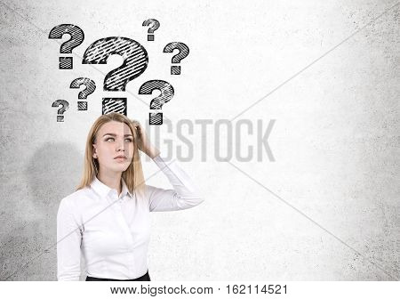 Blond Woman And Question Marks On Concrete Wall