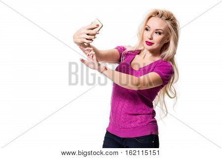 Young blonde doing selfie on isolated white background. Selfie time. Young woman in a lilac blouse