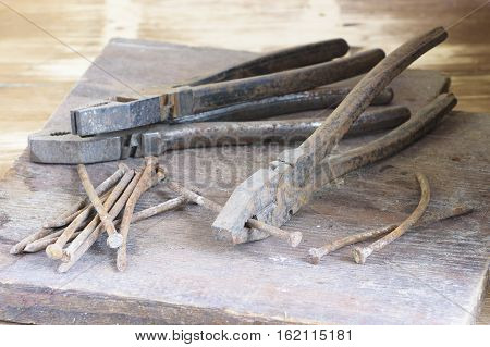 Still life of old rusty hand tools with nails on wooden boards background.
