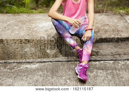 Athletic Girl In Pink Tank Top, Space Print Leggings And Purple Running Shoes Sitting On Curb, Drink