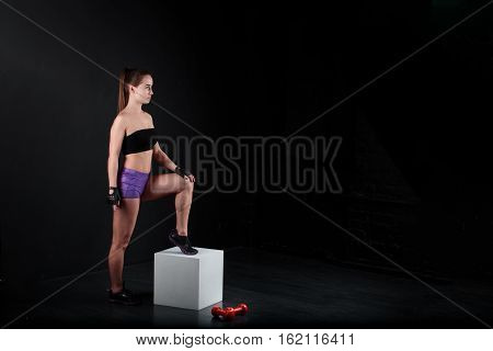 Sport girl stands and looks aside a black background.