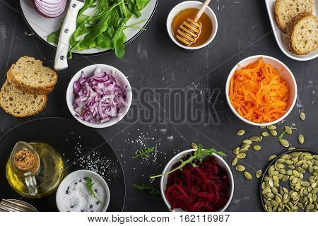 Healthy vegetarian ingredients Carrots, beets, red onion, arugula for fresh salad salads. Top view
