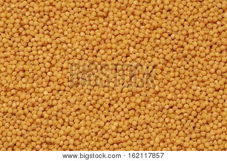 yellow millet groats background on the table top view