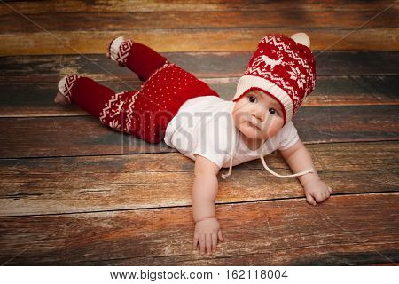 Little baby in red cap of Santa Claus celebrates Christmas. Christmas photo of baby in red cap