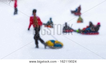 Girl pulls toboggans in one of snowy park, winter leisure, active lifestyles, childhood, Christmas. Selective focus. For background
