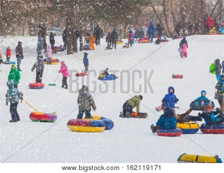 Many children playing tobogganing in the winter down. Selective focus. Concepts of active lifestyles, holiday, winter, Christmas, tobogganing. Selective focus.