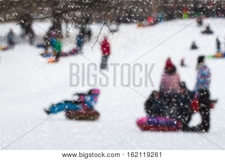 Girls and boys are sleding from the hill in one of snowy park, winter leisure, active lifestyles, childhood, tobogganing, Christmas. Selective focus. For background.
