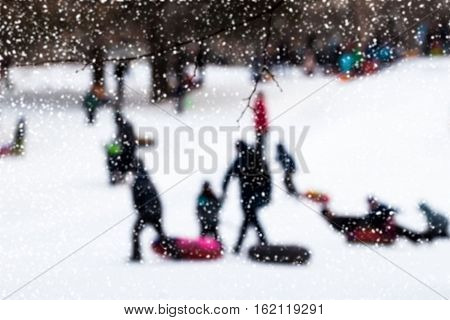 Children with parents pulls toboggans in one of snowy park, winter leisure, active lifestyles, childhood, Christmas. Selective focus. For background.