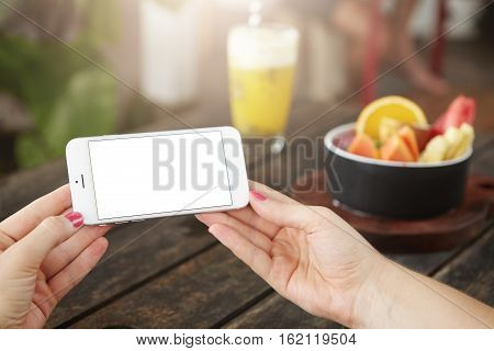 Cropped View Of Woman's Hands Holding Cell Phone With White Copy Space Screen For Your Content. Youn