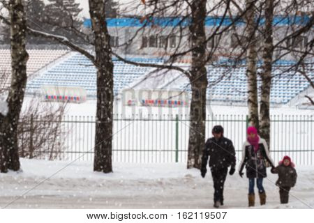 Winter empty stadium. Snow. Family with child on walk. Concepts of active lifestyles, Christmas, New Year. Selective focus