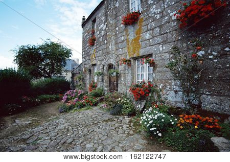 Stone house and flowers garden in brittany Locronan village France