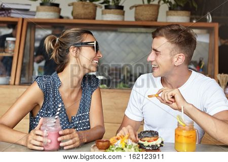 Happy Couple Having Lively Conversation On Their First Date, Having Joyful And Carefree Expressions,