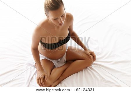 Top View Of Pregnant Woman With Beautiful Tanned Skin Sitting Cross-legged On Bed With White Linen,