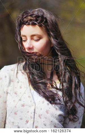 portrait of a very beautiful long haired brunette girl with lowered lashes the jacket on wind ruffling her silky strands and they shut her lips close- up on blurred background