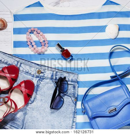 Woman summer clothes, beach outfit, navy blue striped top, jean shorts, blue bag and sunglasses on a wooden background