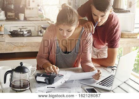Couple Facing Financial Stress. Young Female Dressed Casually Planning Family Budget In Kitchen, Usi