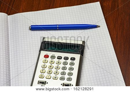 Calculator and blue ballpoint pen lie on a sheet of paper into the cell from a notebook for records