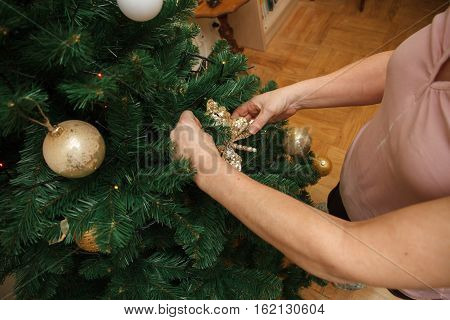 Adult woman, mother, decorating Christmas tree with colorful balls.