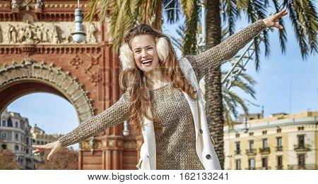 Happy Woman Near Arc De Triomf Walking On Parapet In Barcelona
