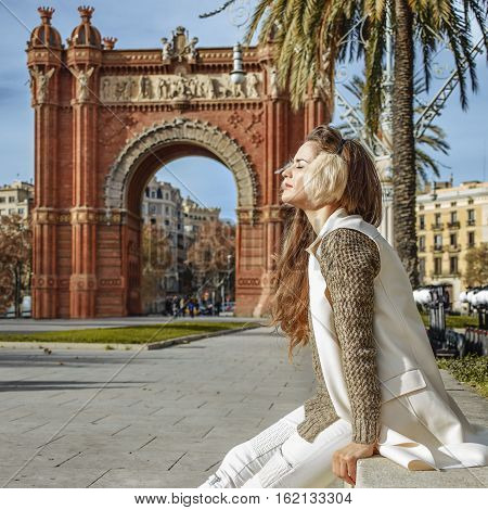 Relaxed Fashion-monger Near Arc De Triomf Sitting On Parapet