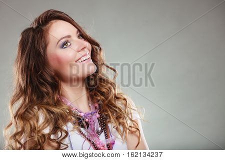 Happy pretty young woman wearing many plenty of jewelry necklaces beads. Portrait of gorgeous fashion girl in studio on gray.