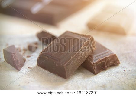 Some ounces of dark chocolate on white wooden table.