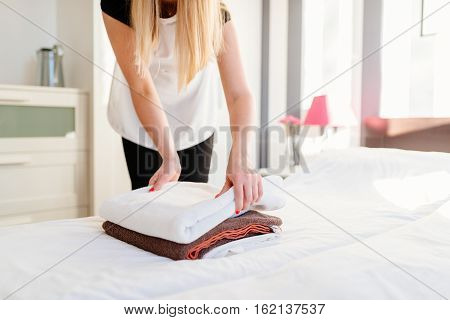 Young Hotel Maid Placing Fresh Towels On A Bed