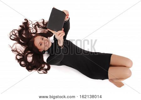 Happy student teenage girl lying on the floor with tablet pc isolated on white