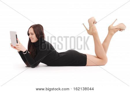 Teenage girl lying on the floor looking at tablet pc isolated on white