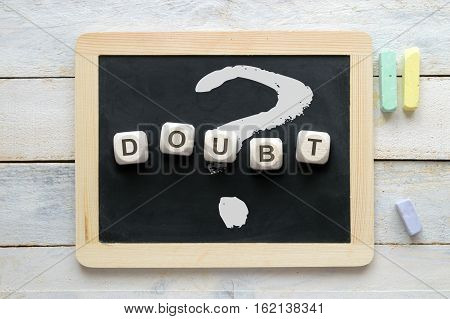 The word DOUBT and the question mark written on a blackboard. Conceptual image.