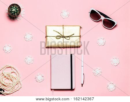 Flat lay, top view Christmas winter decorated table. Feminine desk workspace with snowflakes, pink notebook, white handle, white glasses, gift box on pink background