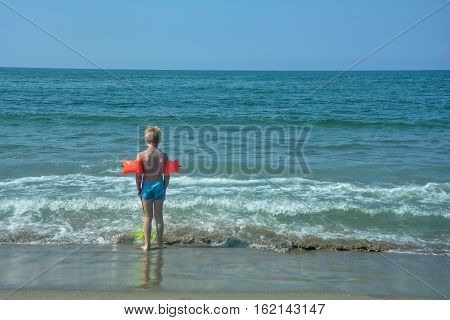 Small blond boy with red swimming sleeves, stands on the beach and looks to the sea
