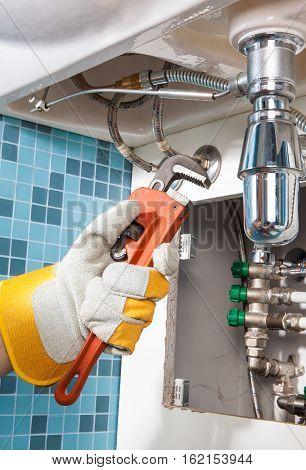 Plumbing work and sanitary engineering repairing a pipe under a sink. Sanitary works.